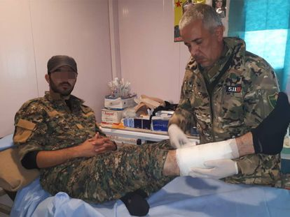 El Doctor Delil atendiendo a un miliciano kurdo herido en su dispensario del campamento de Ahmud, en Sinjar (Irak).