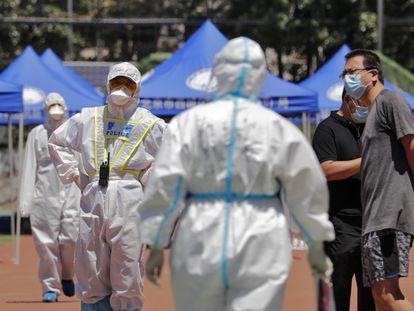 Un policía en traje protector vigila a vecinos del mercado de Xinfadi que acuden a hacerse una prueba de coronavirus en un estadio de Pekín.