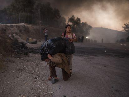Refugiados cargan lo que han podido salvar del fuego en el campo de refugiados de Moria, en la isla griega de Lesbos.