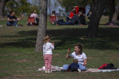 Una mujer con dos niños toma fotos alejada de otros grupos en la Casa de Campo en Madrid.