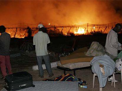 Varios inmigrantes observan el incendio en el invernadero del pueblo almeriense de San Isidro de Níjar, en diciembre de 2019.