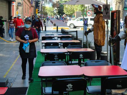 Una trabajadora limpia las mesas de un restaurante en Ciudad de México.