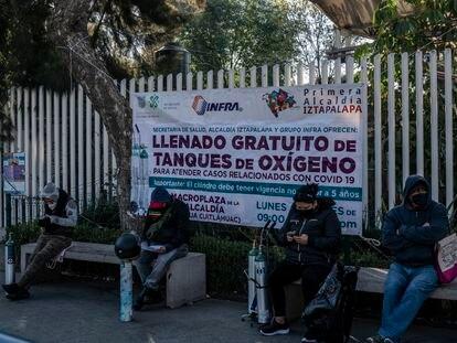 Familiares de enfermos esperan formados un  turno para poder recargar sus tanques de oxigeno en la explanada de la delegación de Iztapalapa.