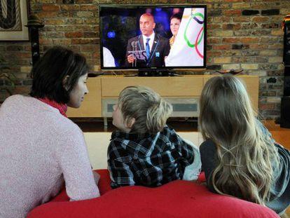 Una familia ve los Juegos Olímpicos por televisión.