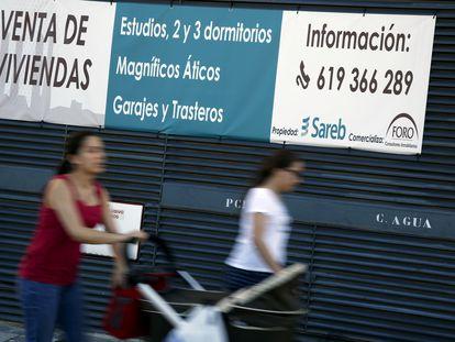 Carteles anunciando la venta de viviendas en un edificio propiedad de Sareb en Madrid.