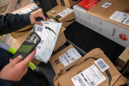 Un repartidor prepara pedidos de Amazon en su coche frente al centro logístico de Amazon de Alcobendas (Madrid).
