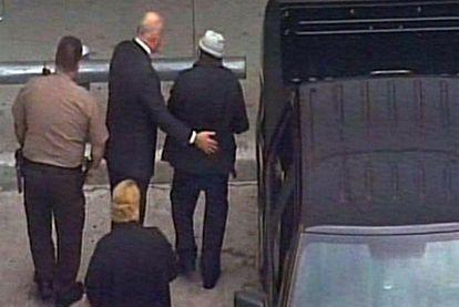 Noriega, con sombrero, es conducido al avión en el aeropuerto de Miami.