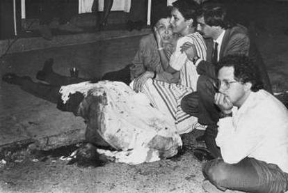 Héctor Abad Faciolince, with his hand on his chin, next to the body of his father, Héctor Abad Gómez, murdered in Medellín on August 25, 1987.