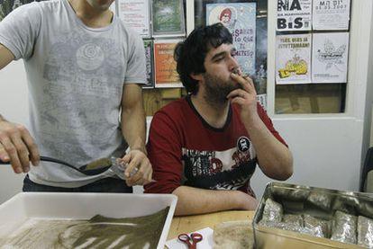 Dos socios de Pannagh en la sede de la asociación en Bilbao. Uno fuma marihuana, mientras el otro empaqueta bolsas de hachís que, posteriormente, prensa para una mejor conservación.