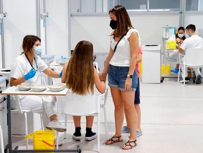 Una adolescente, acompañada de su madre, se vacuna contra la covid-19 en el hospital Enfermera Isabel Zendal de Madrid, este miércoles.