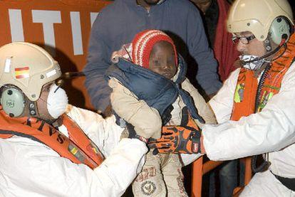 Miembros de Salvamento Marítimo trasladan a uno de los niños que viajaban en la embarcación.