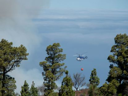 Uno de los helicópteros que participan este domingo en las labores de extinción del incendio forestal de La Palma realiza una maniobra de aproximación para apagar un foco reavivado por el viento en el cortafuego de la localidad de Las Palomas, en el municipio de Garafía.