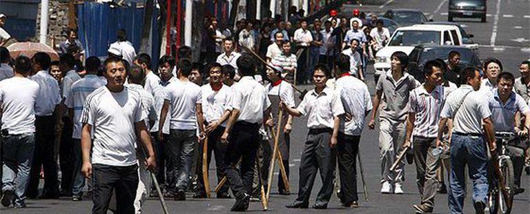 Un grupo de hanes (etnia mayoritaria de China) armado con palos y piedras pretenden agredir a los miembros de la minoría uigur a los que acusan de la destrucción de sus comercios.