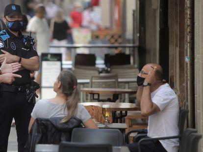 Dos agentes de la Policía Local de A Coruña se dirigen a un hombre que fuma en una terraza, este jueves.