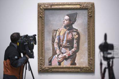 Un cámara ante el cuadro 'Arlequin sentado', de Picasso, en el Prado.