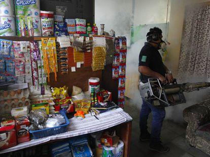 Un empleado del Ministerio de Salud de El Salvador fumiga una casa.