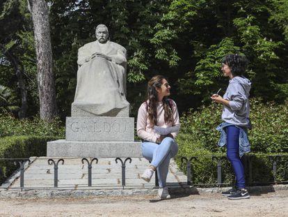 Dos chicas charlan junto a la estatua de Pérez Galdós en el Retiro.