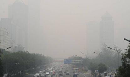 Imagen diaria en Pekín: el 'smog' reina sobre una de sus innumerables autopistas