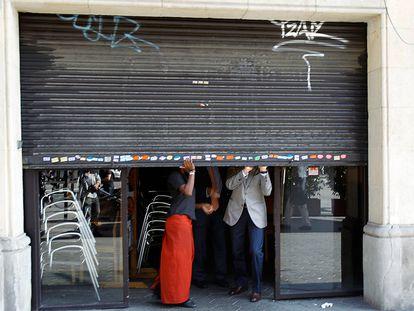 Unos trabajadores bajan la persiana de un bar en Barcelona.