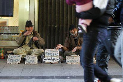 Lyndon Owen y José Manuel Calvo García piden limosna, ayer en la calle del Carmen.