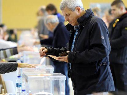 Un vecino votando en un colegio electoral de Girona