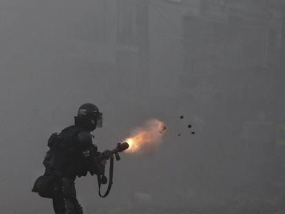 Un oficial de la policía lanza gases lacrimógenos a los manifestantes durante la huelga contra la reforma fiscal en Cali.