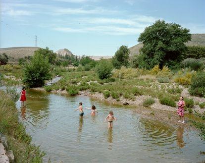 """Un grupo de bañistas en el río Grío, un afluente del Jalón, en la provincia de Zaragoza. Una vecina, María Pilar Pellicer, nos dijo: """"Maño, esto era un bum el verano pasado, porque la gente casi no se movió en vacaciones y solo teníamos el río""""."""
