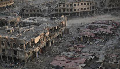 Varias personas caminan entre la ruinas de un barrio de Mosul.