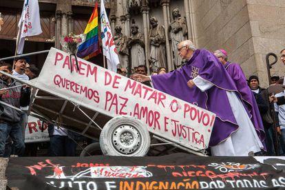 El padre Júlio Lancelotti, de la Pastoral del Pueblo de la Calle, bendice la carreta de Ricardo Nascimento.