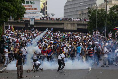 Un grupo de manifestantes se enfrenta con la policía hoy en Caracas.