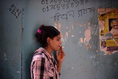 La trabajadora sexual Munni fuma un cigarrillo fuera de su habitación antes de atender a un cliente en el burdel de Kandapara, en Tangail.