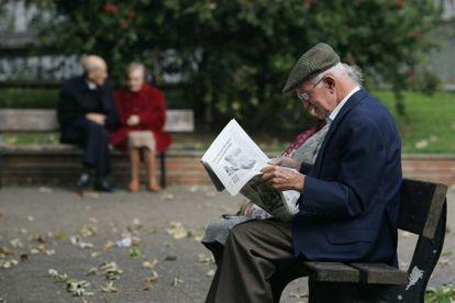 Un jubilado lee un periódico en un parque.