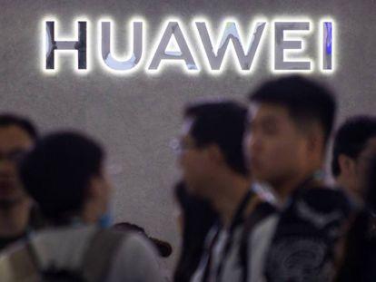 Varias personas frente a un logo de Huawei en Shanghái.