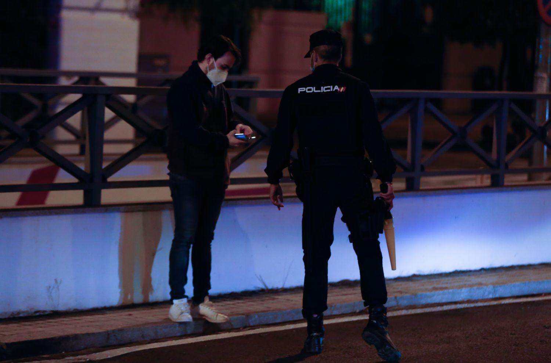Un policía nacional para a un ciudadano a las 23.00, este miércoles en Madrid.