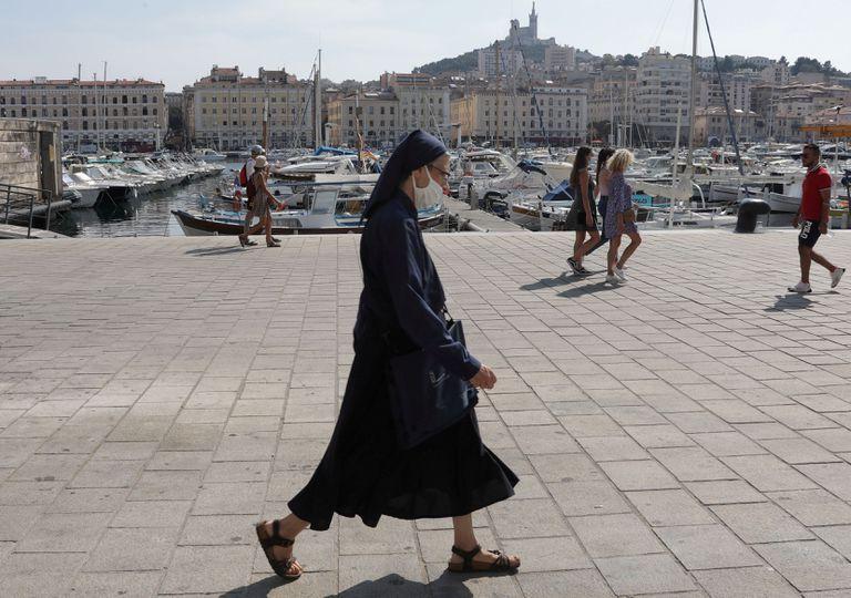 Una monja camina con mascarilla por el viejo puerto de Marsella