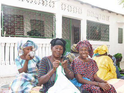 Mujeres sentadas esperan que comience la reunión, tomando café, hablando y haciendo ganchillo en el patio de Fatou Thiam.