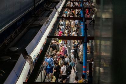 Decenas de pasajeros esperan para subir a un vagón de la línea 10 del metro de Madrid en Príncipe Pío, a finales de agosto.