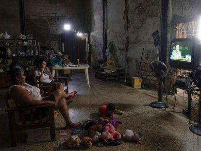 Una familia mira las noticias de la televisión local que muestran al primer secretario del Partido Comunista de Cuba y ex presidente Raúl Castro dirigiéndose a la audiencia de la sesión inaugural del VIII Congreso del Partido Comunista de Cuba.