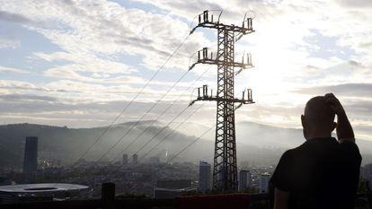 Una persona observa el cableado con el que red eléctrica transporta la energía sobre la ciudad de Bilbao.