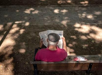 Un hombre mayor, sentado solo en un banco, lee el periódico en un parque de Madrid el pasado viernes.