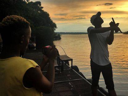 Dos turistas se hacen fotos durante el atardecer a orillas del río Chobe, frontera natural entre Botsuana y Namibia.