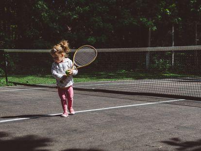 Una niña juega al tenis a pleno sol.