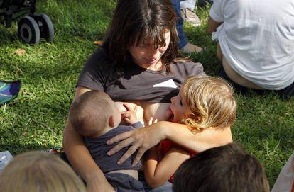 Una madre da de mamar a dos niños.