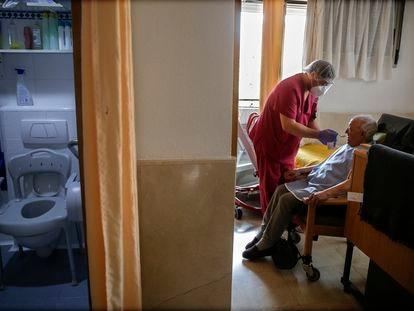 Un empleado cuida de un hombre mayor en una de las habitaciones en la residencia de ancianos Santa María de Montecarmelo, en Madrid.