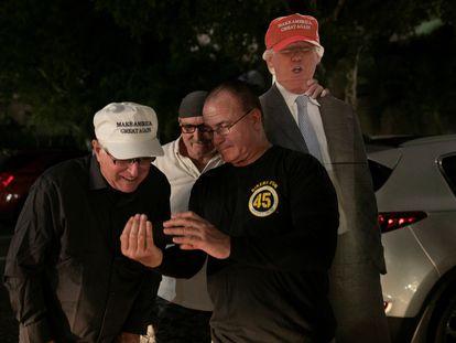 Partidarios del presidente de Estados Unidos, Donald Trump, miran un teléfono mientras esperan a que pase en su caravana, en West Palm Beach, Florida.