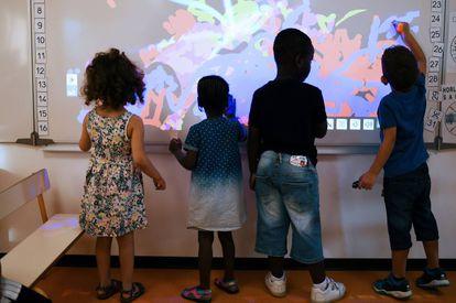 Alumnos juegan con una pizarra digital en un colegio de Capelette, Marsella.