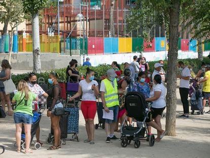 Decenas de vecinos hacen cola en el barrio de Aluche para recoger una bolsa con alimentos este sábado.