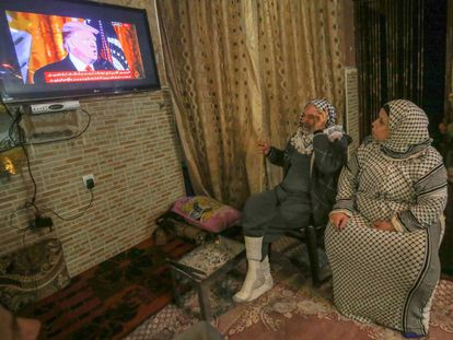 Dos palestinos ven al presidente estadounidense, Donald Trump, hablando por televisión el pasado 28 de enero.