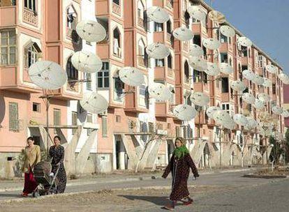 Unas mujeres pasean por delante de un edificio de viviendas plagado de antenas parabólicas en Turkmenabat.