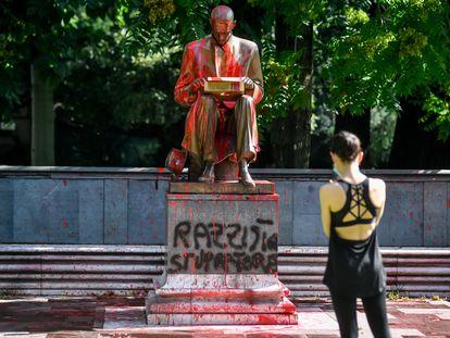 Una mujer hace una foto de la estatua de Indro Montanelli en Milán, atacada con pintadas que lo acusan de racista y violador.